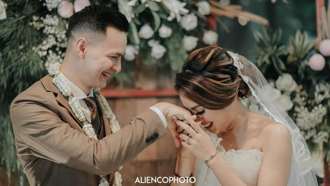 Senyuman semringah terlukis di wajah Marcell dan Nabila. Seperti di foto ini, Nabila begitu bahagia saat mencium tangan laki-laki yang telah resmi menjadi suaminya. (Instagram/aliencophoto)