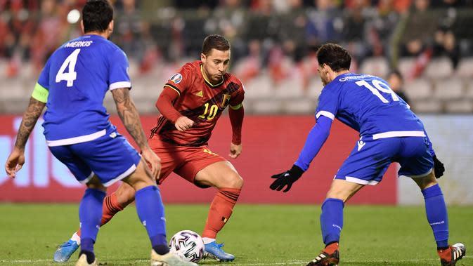 Kapten Timnas Belgia, Eden Hazard berebut bola dengan pemain Timnas Siprus, Christoforou Kypros pada laga Grup I Kualifikasi Piala Eropa 2020 di Stade Roi Baudouin, Selasa (19/11/2019). Timnas Belgia memetik kemenangan telak dengan skor 6-1 kala menjamu Siprus. (JOHN THYS / AFP)