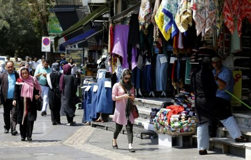 People walk in a shopping street in the Iranian capital Tehran on August 6, 2018