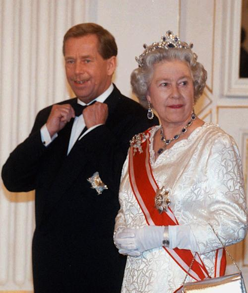 FILE - Czech President Vaclav Havel adjusts his bow-tie as he accompanies Britain' s Queen Elizabeth II to the state banquet in the Spanish Hall of Prague Castle late in this March 27, 1996 file photo. Havel wears the Knight Grand and Cross of the Order of the Bath he received from the queen on the first day of her visit to the Czech Republic. Havel, the dissident playwright who wove theater into politics to peacefully bring down communism in Czechoslovakia and become a hero of the epic struggle that ended the Cold War, died Sunday Dec. 18, 2011 in Prague. He was 75. (AP Photo/Tomas Turek/CTK, File)