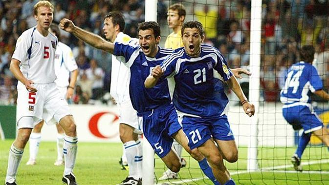 Bek Yunani, Traianos Dellas (kiri) usai mencetak gol penentu kemenangan 1-0 atas Ceska pada semifinal Piala Eropa 2004, di Estadio do Dragao, 1 Juli 2004. (UEFA).