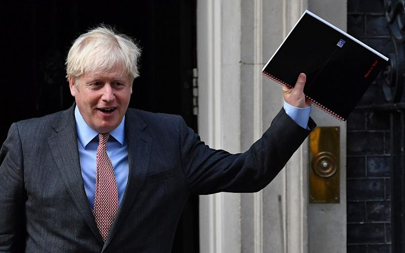 Boris Johnson reacts as he leaves 10 Downing Street as the government upgraded its coronavirus alert level - BEN STANSALL/AFP