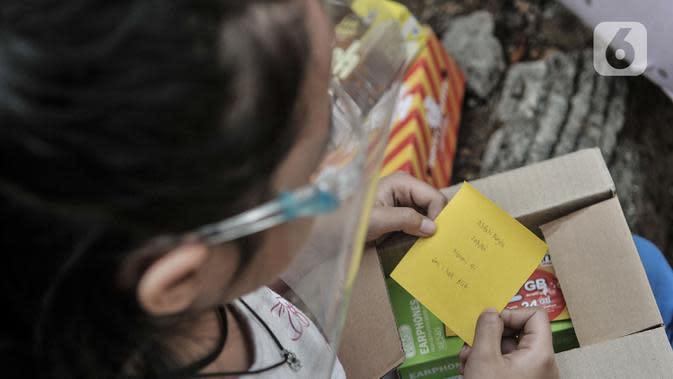 Seorang anak membuka boks donasi ponsel yang diberikan oleh Komunitas #WartawanLintasMedia saat acara #PonselPintarUntukPelajar di Jakarta, Minggu (9/8/2020). (merdeka.com/Iqbal S. Nugroho)