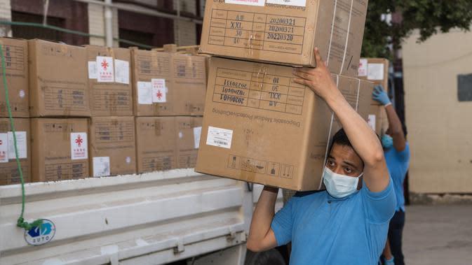 Para pekerja memindahkan pasokan medis sumbangan dari China di Kairo, Mesir (10/5/2020). Mesir pada Minggu (10/5) menerima kelompok pengiriman bantuan medis kedua dari pemerintah China bagi negara di kawasan Afrika Utara tersebut untuk memerangi wabah Covid-19. (Xinhua/Wu Huiwo)