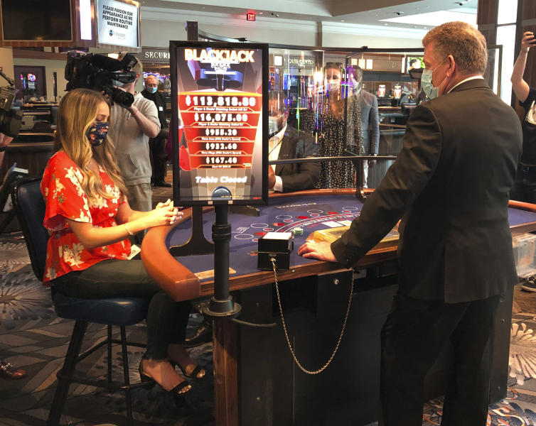In this May 22, 2020 photo, a blackjack dealer at Foxwoods Resort Casino in Mashantucket, Conn., demonstrates to reporters on how new protective measures, including plastic shields, will work when the tribal-owned Foxwoods and neighboring Mohegan Sun expect to partially reopen on June 1. The Mashantucket Pequot and Mohegan Tribes are pushing ahead with plans to open their resorts on tribal lands, despite opposition from Connecticut Gov. Ned Lamont. (AP Photo/Susan Haigh)