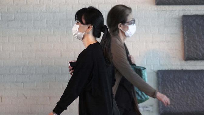 Wanita yang mengenakan masker pelindung untuk membantu mengekang penyebaran virus corona COVID-19 berjalan di Tokyo, Jepang, Jumat (16/10/2020). Tokyo mengonfirmasi lebih dari 180 kasus virus corona COVID-19 baru pada hari Jumat. (AP Photo/Eugene Hoshiko)