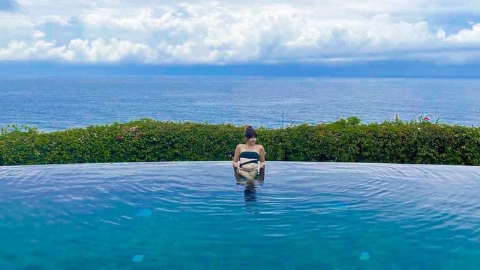 Perempuan tiga orang anak itu menikmati berendam di kolam renang di salah satu villa mewah. Terlihat di belakang nia pantai dengan indah membentang jauh dengan awan putih di atasnya. (Instagram/ramadhaniabakrie)