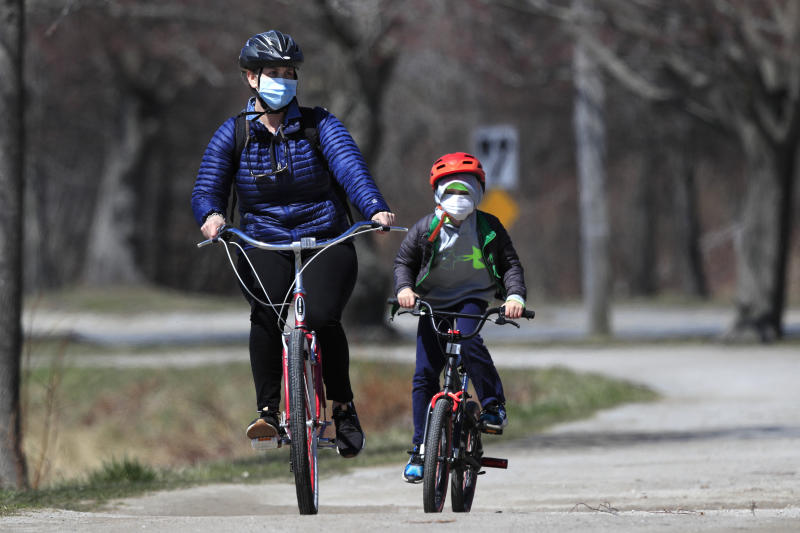 FILE-In this Wednesday, April 8, 2020, photo, bicyclists wear pandemic masks while riding in Portland, Maine. Bicycle sales have surged as shut-in families try to find a way to keep kids active at a time of lockdowns and stay-at-home orders during the coronavirus pandemic. (AP Photo/Robert F. Bukaty)