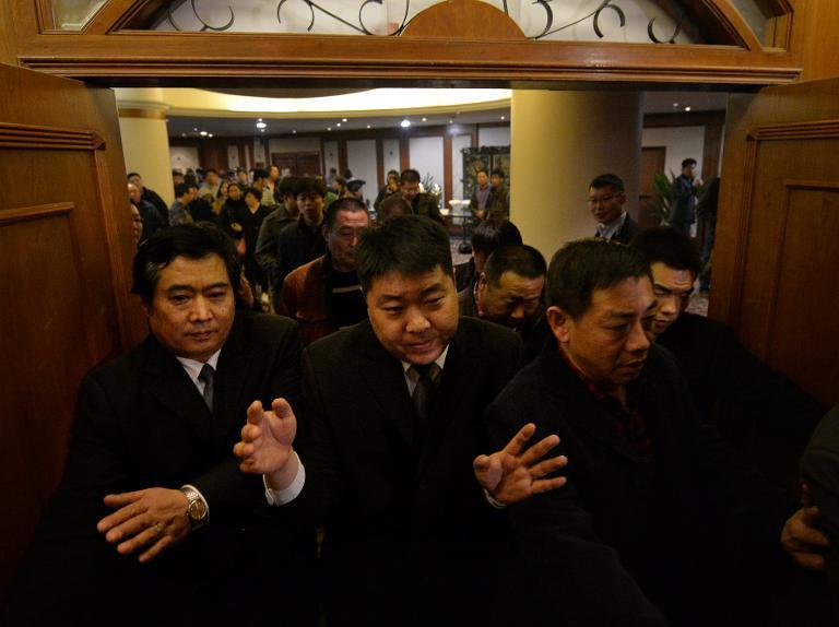 Security blocks journalists from the meeting with relatives of passengers from the missing Malaysia Airlines Boeing 777-200 plane and the Malaysian ambassador at the Metro Park Lido Hotel in Beijing on March 12, 2014