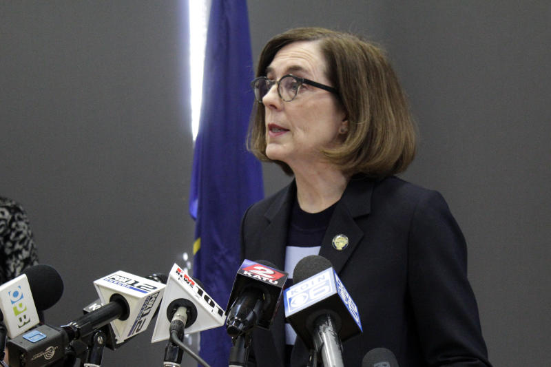 """FILE - In this Monday, March 16, 2020 file photo, Gov. Kate Brown speaks at a news conference to announce a four-week ban on eat-in dining at bars and restaurants throughout the state in Portland, Ore., to slow the spread of the new coronavirus. """"I am gravely concerned about our ability to deliver basic services over the next six months to a year given the drop in revenues, and that's why I am encouraging the Legislature to be extremely fiscally prudent,"""" Brown, a Democrat, said about building the budget for the coming fiscal year. (AP Photo/Gillian Flaccus)"""