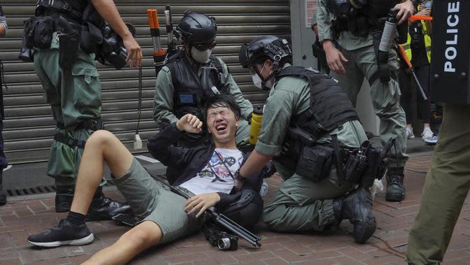 Seorang wartawan jatuh setelah disemprot dengan semprotan merica oleh polisi dalam unjuk rasa menentang Undang-Undang Keamanan Nasional pada hari peringatan penyerahan Hong Kong ke China dari Inggris di Hong Kong, Rabu (1/7/2020). (AP Photo/Vincent Yu)