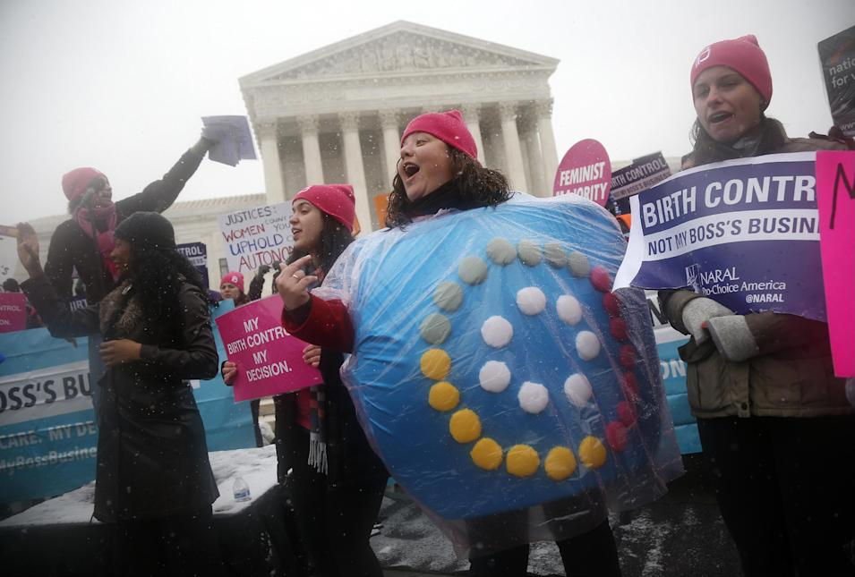 Margot Riphagen of New Orleans, La., wears a birth control pills costume as she protests in front of the Supreme Court in Washington, Tuesday, March 25, 2014, as the court heard oral arguments in the challenges of President Barack Obama's health care law requirement that businesses provide their female employees with health insurance that includes access to contraceptives. Supreme Court justices are weighing whether corporations have religious rights that exempt them from part of the new health care law that requires coverage of birth control for employees at no extra charge. (AP Photo/Charles Dharapak)