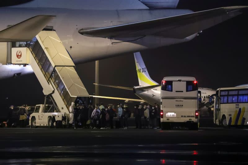 Passengers of the cruise ship Diamond Princess, where dozens of passengers were tested positive for coronavirus, board their plane at Haneda airport in Tokyo
