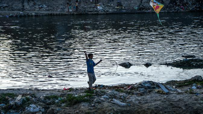 Seorang anak menerbangkan layang-layang di tepi sungai menjelang festival Hindu Dashain di Kathmandu (7/10/2020). Festival ini jatuh pada bulan September atau Oktober, dimulai dari shukla paksha (dua minggu bulan cerah) di bulan Ashwin dan berakhir pada Purnima, bulan purnama. (AFP/Prakash Mathema)