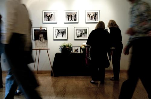 """Patrons of Andy Williams' memorial service look at pictures of Williams at the Moon River Theater, in Branson, Mo., Sunday, Oct. 21, 2012. Williams, known for singing """"Moon River"""" and his Christmas television specials, passed away Sept. 25. (AP Photo/Grant Hindsley)"""