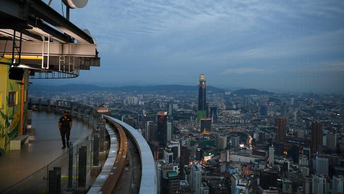 Seorang penjaga keamanan berpatroli di sepanjang Menara KL di Kuala Lumpur (13/10/2020). Malaysia tengah memerangi lonjakan baru kasus virus corona baru COVID-19. (AFP/Mohd Rasfan)