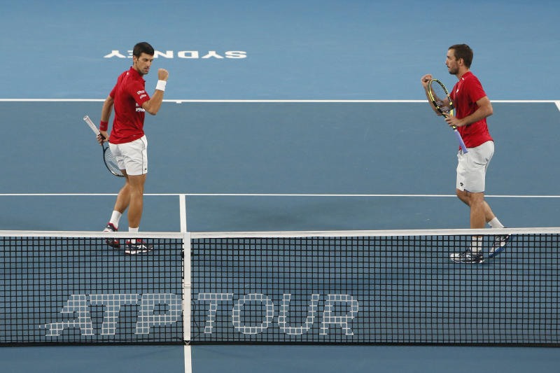 Novak Djokovic, left, and Viktor Troicki of Serbia react to a point against Pablo Carreno Busta and Feliciano Lopez of Spain come together during their ATP Cup tennis match in Sydney, Monday, Jan. 13, 2020. (AP Photo/Steve Christo)