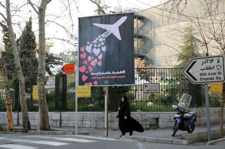 An Iranian woman walks beneath a poster outside Amirkabir University honouring the victims of the Ukrainian passenger jet accidentally shot down by Tehran