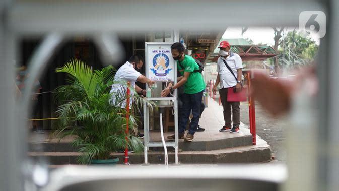 Pengunjung mencuci tangan saat masuk ke kawasan Pasar Minggu, Jakarta, Selasa (23/6/2020). Pascapenutupan tiga hari terkait ditemukannya tiga pedagang yang positif COVID-19, pengunjung Pasar Minggu kini diwajibkan mencuci tangan dan cek suhu tubuh. (Liputan6.com/Immanuel Antonius)