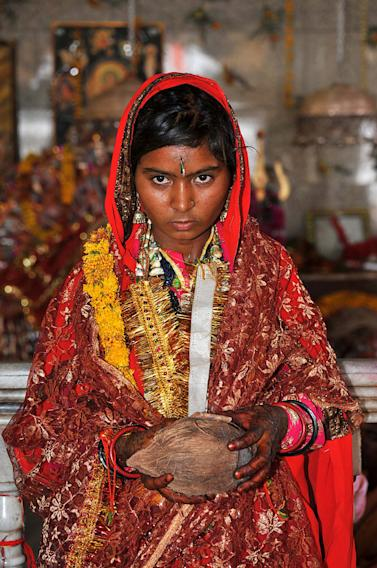 In this Friday, May 6, 2011 photo, child bride Smita,13, from  Raghogarh village, looks on at the Maa Jalapa Devi temple after her marriage ceremony in Rajgarh, about 155 kilometers (96 miles) from Bhopal, India. Ignoring laws that ban child marriages, several young children, are still married off as part of centuries-old custom in some Indian villages. India law prohibits marriage for women younger than 18 and men under age 21. (AP Photo/Prakash Hatvalne)