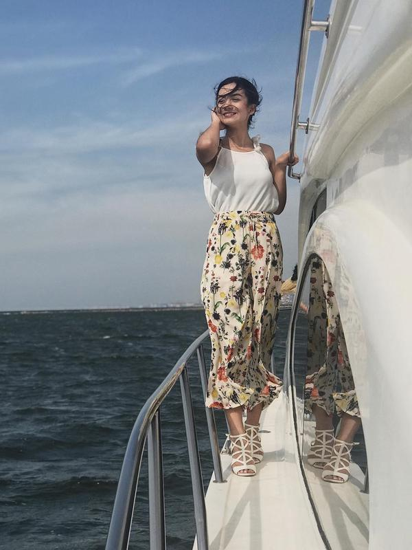 Ia juga menikmati hembusan angin ketika berada di atas kapal. Meski rambutnya berantakan diterpa angin, Ersya tetap cantik dengan balutan atasan putih tanpa lengan dan bawahan bermotif. Makin anggun dengan sepatu bertali. (Liputan6.com/IG/@ersyaurel)