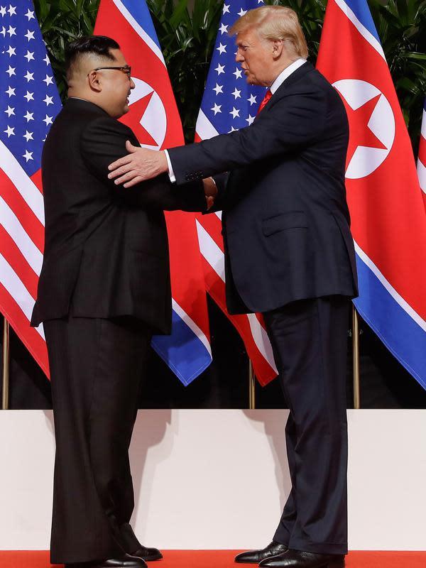 Presiden AS Donald Trump berjabat tangan dengan Pemimpin Korea Utara, Kim Jong-un dalam pertemuan bersejarah di resor Capella, Pulau Sentosa, Selasa (12/6). Kim dan Trump hadir di depan jurnalis dengan latar belakang bendera Korut dan AS. (AP/Evan Vucci)