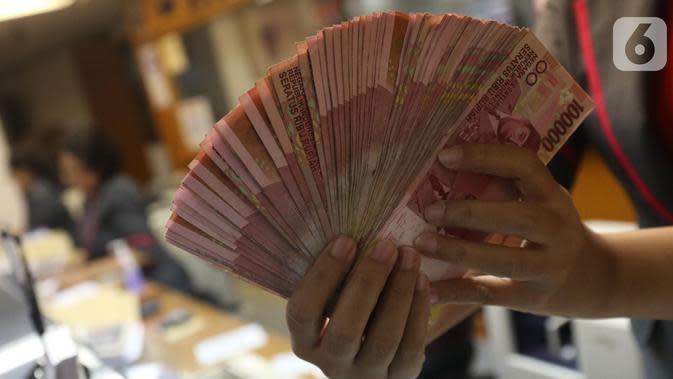 Teller menunjukkan mata uang rupiah di Jakarta, Selasa (15/10/219). Rupiah di pasar spot ditutup di level Rp 14.166 per dolar AS. (Liputan6.com/Angga Yuniar)