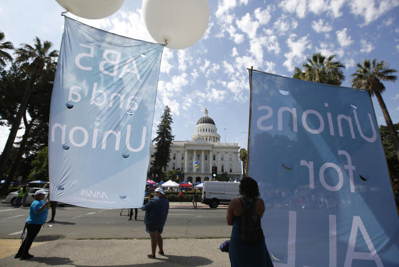 Supporters of a measure to limit when companies can label workers as independent contractors display banners in support of the bill during a rally at the Capitol in Sacramento, Calif., Wednesday, Aug. 28, 2019. If approved by the legislature and signed by Gov. Gavin Newsom, AB5, by Assemblywoman Lorena Gonzalez, D-San Diego, would require companies like Uber and Lyft to treat their drivers like employees. (AP Photo/Rich Pedroncelli)