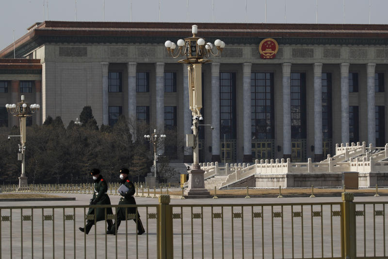 In this Sunday, Feb. 23, 2020, photo, paramilitary policemen wearing protective face masks walk by the empty Tiananmen Square against the back drop of the Great Hall of the People in Beijing. China announced Monday it has postponed its most important political meeting of the year because of the outbreak of the new virus. (AP Photo/Andy Wong)