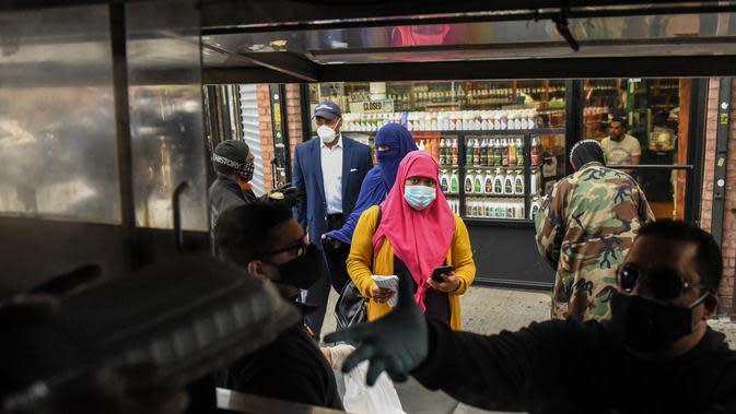 Orang-orang mengantre makan Halal gratis untuk Iftar selama bulan suci Ramadan di depan Masjid Taqwa di Bedford-Stuyvesant, Brooklyn, New York (14/5/2020). Acara ini diorganisir oleh Wakil Advokat Publik Kashif Hussain bersama Presiden Borough Brooklyn, Eric Adams. (Stephanie Keith/Getty Images/AFP)
