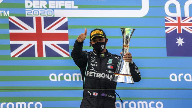 Pembalap Mercedes Lewis Hamilton memegang trofi setelah memenangkan F1 GP Eifel di Nuerburgring, Nuerburg, Jerman, Minggu (11/10/2020). Hamilton dengan 91 kemenangannya menyamai legenda F1 Michael Schumacher. (Wolfgang Rattay, Pool via AP)