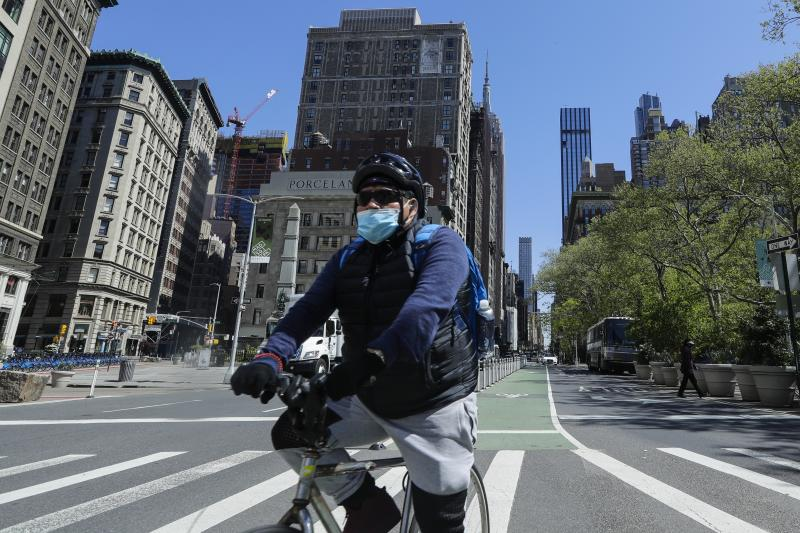 A cyclist wears a protective mask as they pass Madison Square Park, Tuesday, May 12, 2020, in New York. (AP Photo/Frank Franklin II)