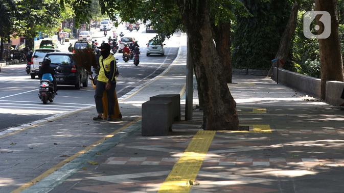 Petugas kebersihan di pedestrian seputaran Istana dan Kebun Raya Bogor, Jawa Barat, Sabtu (19/9/2020). Sebagai upaya pencegahan penularan COVID-19, Pemkot Bogor menutup sementara pedestrian seputaran Istana dan Kebun Raya Bogor pada Sabtu dan Minggu di masa PSBMK. (Liputan6.com/Helmi Fithriansyah)