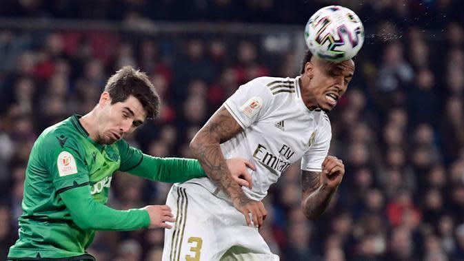 Pemain Real Sociedad, Aritz Elustondo (kiri) berebut bola dengan bek Real Madrid, Eder Militao pada laga perempat final Copa del Rey di Santiago Bernabeu, Kamis (6/2/2020). Real Madrid gagal melaju ke semifinal Copa del Rey setelah dibungkam Real Sociedad dengan skor 3-4. (JAVIER SORIANO/AFP)