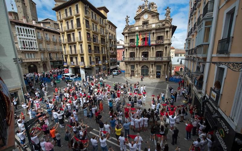People celebrate the suspended 'Chupinazo' opening ceremony to mark what was supposed to be the kick-off of the San Fermin Festival outside the Town Hall of Pamplona in northern Spain - AFP
