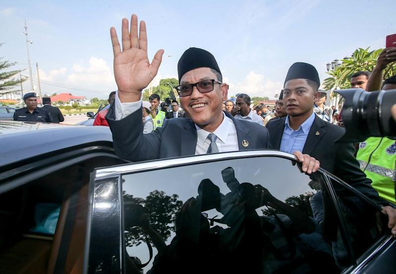 Datuk Seri Ahmad Faizal Azumu waves to reporters as he leaves Istana Kinta March 10, 2020. — Picture by Farhan Najib