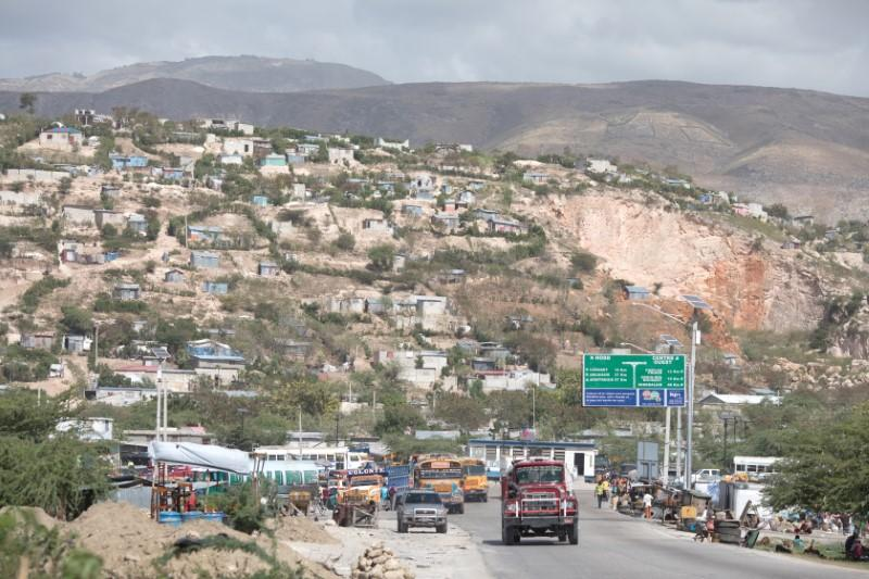 Vehicles drive along the road as Canaan in seen in the background, on the outskirts of Port-au-Prince