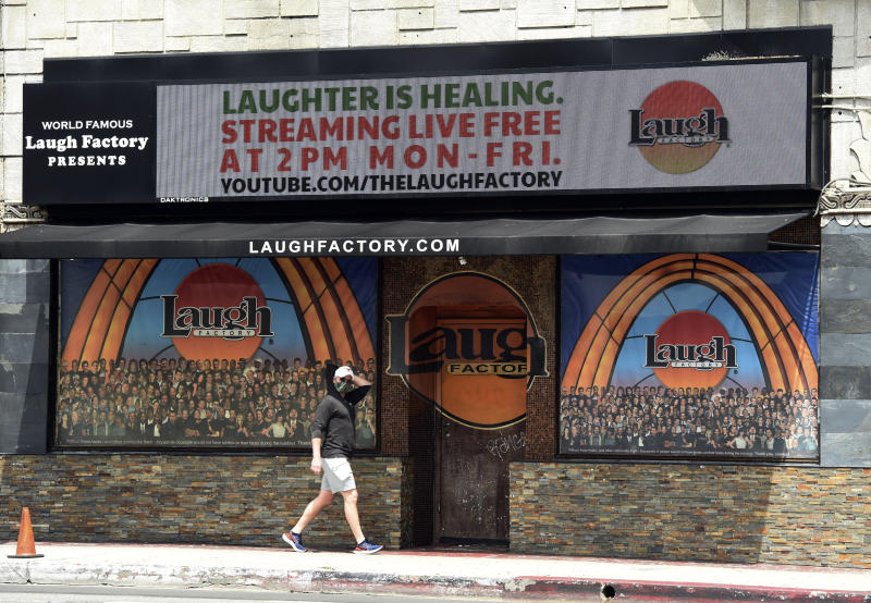 """In this April 20, 2020 photo, a pedestrian walks underneath a marquee advertising a """"Laughter is Healing"""" stand-up comedy livestream event at the Laugh Factory in Los Angeles. With comedy clubs closed and concert tours put on hold, comics like Craig Robinson, Tiffany Haddish, Will C  and others are keeping the jokes flowing on webcasts and Zoom calls even without the promise of a payday, because they say the laughs are needed now more than ever.(AP Photo/Chris Pizzello)"""