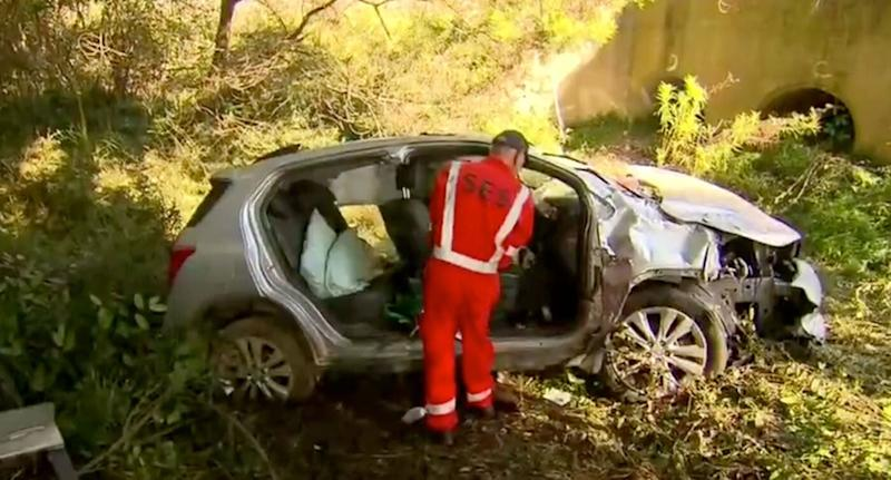 The wreckage of Lynette Williams' car is inspected by an SES worker.