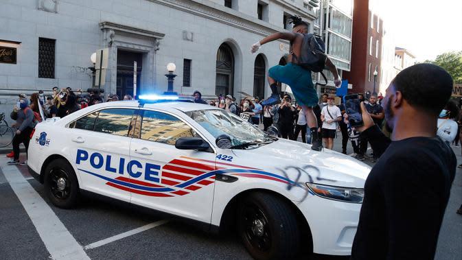 Seorang demonstran merusak mobil polisi saat unjuk rasa di dekat Gedung Putih di Washington (31/5/2020). Demonstran turun ke jalan-jalan di New York City memprotes kematian George Floyd pada (25/5) setelah dijepit di leher oleh seorang petugas kepolisian Minneapolis. (AP Photo/Alex Brandon)