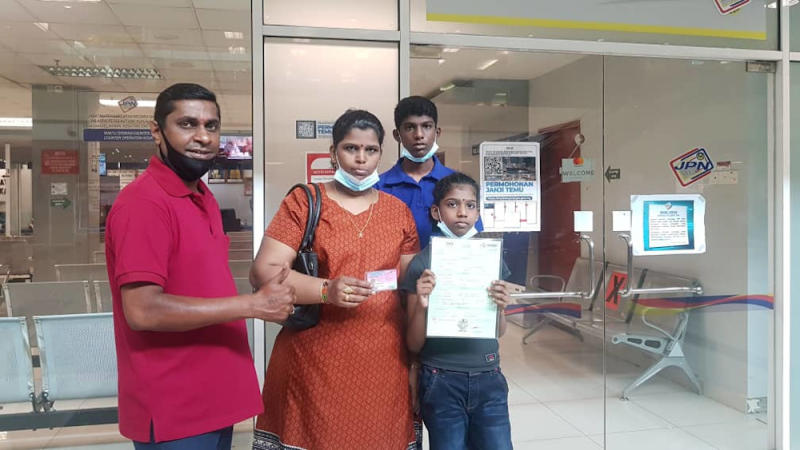 Karthiyani Ragunathan, 10, received her birth certificate and her MyKID (an identity card for Malaysian children aged below 12) on August 5, 2020. Seen here are her mother, her brother and activist Shanmugam Narayanasamy who assisted in their case. — Picture courtesy of Shanmugam Narayanasamy