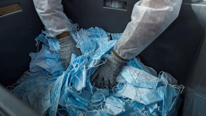 Pekerja menyiapkan masker bekas untuk didaur ulang di perusahaan Plaxtil, Chatellerault, Prancis, 25 Agustus 2020. Startup di Prancis, Plaxtil, mendaur ulang masker dan plastik untuk dijadikan pelindung wajah, pembuka pintu, dan pengencang masker. (GUILLAUME SOUVANT/AFP)