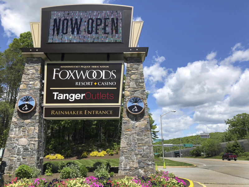 A sign at the entrance to the Foxwoods Resort Casino, in Mashantucket, Conn., announces its reopening, Monday, June 1, 2020. Both tribal casinos, Foxwoods and Mohegan Sun, closed since March 17, opened despite opposition from Connecticut Gov. Ned Lamont, who has limited power regarding the sovereign nations. (AP Photo/Susan Haigh)