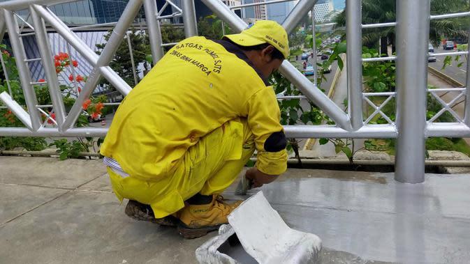 Petugas mengecat JPO tanpa atap di Jalan Sudirman, Jakarta Rabu (6/11/2019). (Liputan6.com/ Rizki Putra Aslendra)