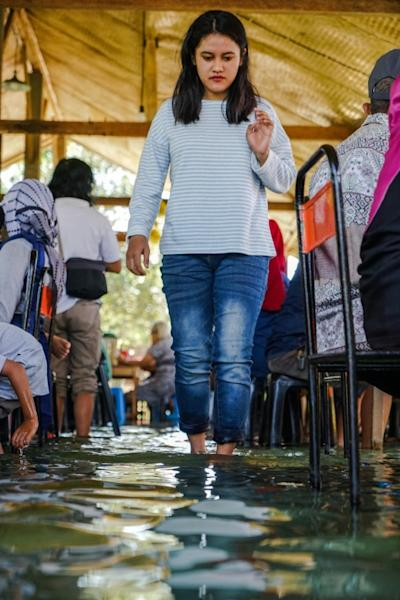 A diner wades through a fish pond to her table to have a lunch while fish nibble at her feet at a restaurant in Indonesia