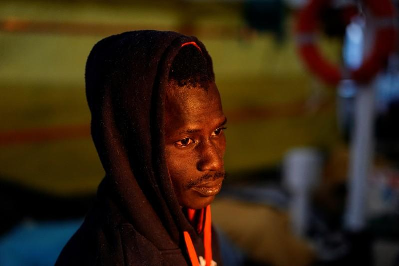 A migrant rests on board of NGO Proactiva Open Arms rescue boat in central Mediterranean Sea