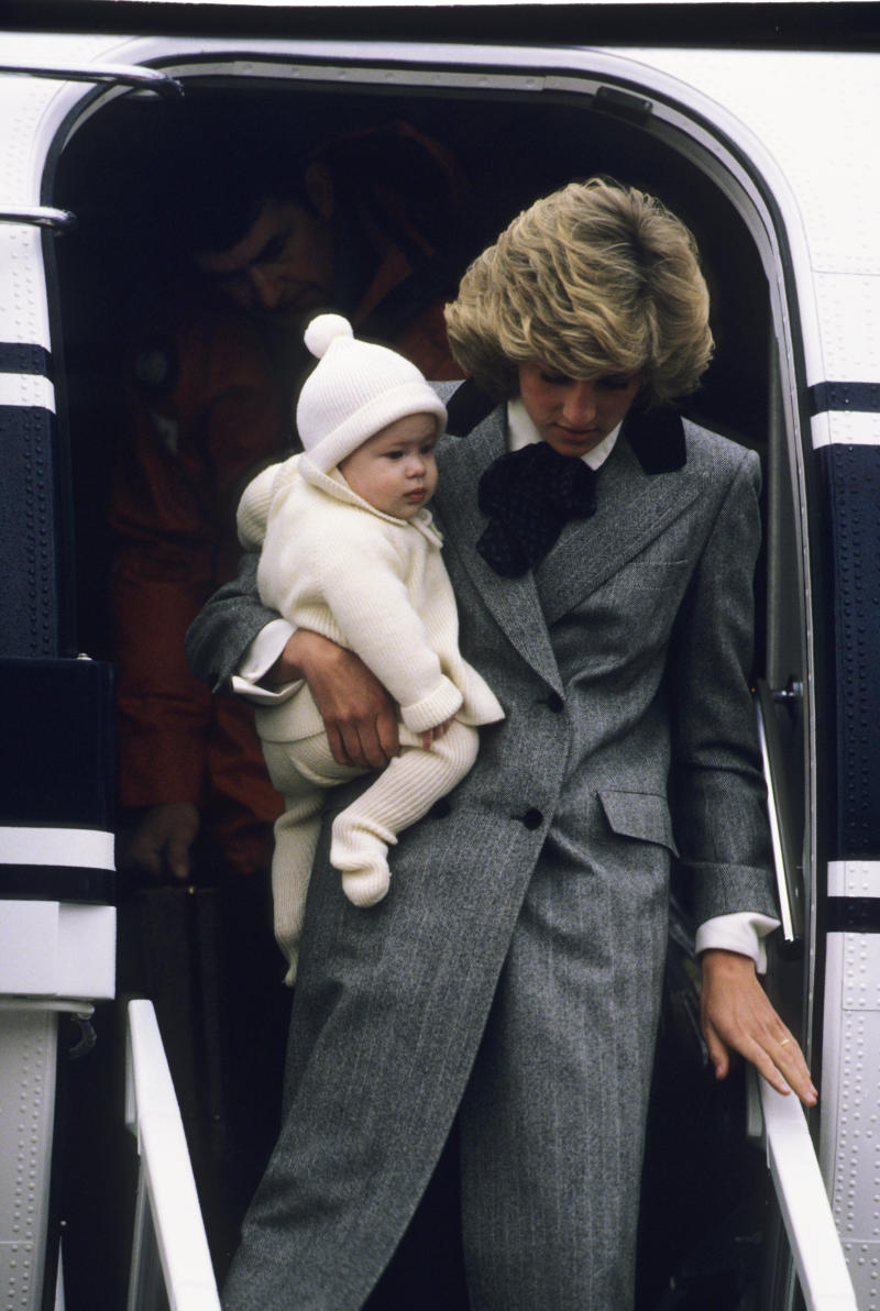 Diana, Princess of Wales carries her son, Prince Harry, off a flight at Aberdeen Airport