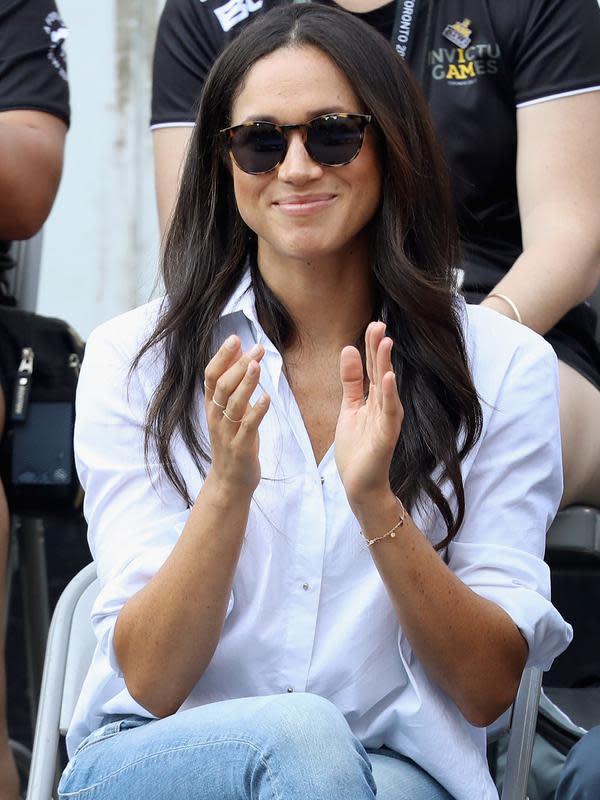 Kekasih Pangeran Harry yang juga aktris, Meghan Markle menonton pertandingan tenis kursi roda selama Invictus Games 2017 di Toronto, Kanada, Senin (25/9). Meghan tampil lebih kasual dengan kemeja putih dan jeans skinny. (Chris Jackson/GETTY IMAGES/AFP)