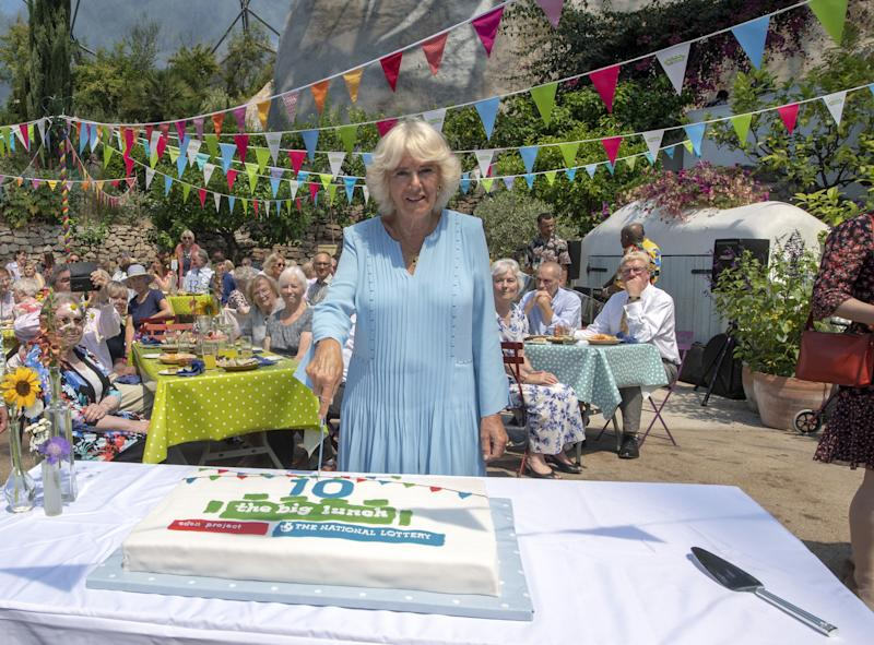 TOPSHOT - Britain's Camilla, Duchess of Cornwall poses for a photograph as she cuts a birthday cake as she attends the tenth anniversary celebration of The Big Lunch initiative at the Eden Project in south west England on July 15, 2019. - The Big Lunch is Edens biggest outreach project, since 2009 it has brought people together with their neighbours for a few hours of community, friendship and fun. (Photo by ARTHUR EDWARDS / POOL / AFP) (Photo by ARTHUR EDWARDS/POOL/AFP via Getty Images)