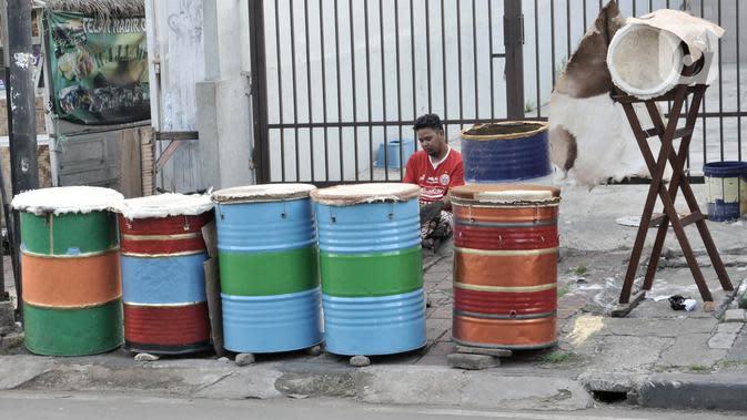 Penjual beduk menunggu pembeli di kawasan Tanah Abang, Jakarta, Selasa (19/5/2020). Pedagang mengaku memasuki seminggu jelang Lebaran penjualan beduk hanya mencapai puluhan, berbeda jauh dengan tahun lalu yang mampu menjual hingga ratusan beduk. (merdeka.com/Iqbal Nugroho)